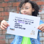 A young girl holding up her mission statement mentor through media